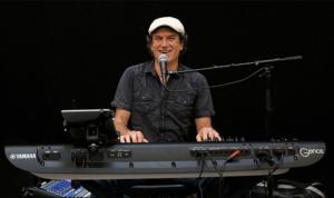 livemusiker dave sitzt am Keyoard und lacht